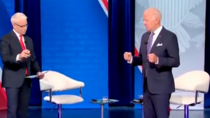 The Biden Holds Out Fists in a Grip While Standing Straight